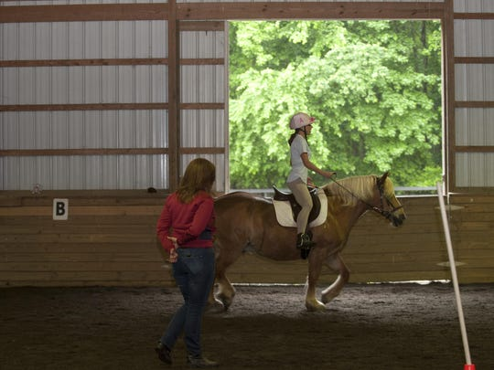 Trainer Sherri Briggs looks over Bridgid Cain as she rides on horse Cocoa during a lesson at Compassionate Friends Therapeutic Riding Center in Medford in 2015.