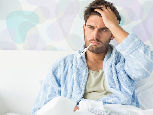 Sick man with thermometer in mouth sitting on bed