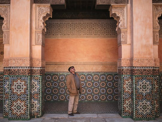 A tourist admires the columns of Ben Youssef Madrasa,