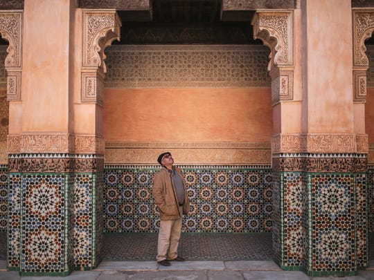 A tourist admires the columns of Ben Youssef Madrasa,