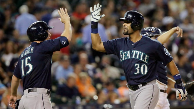 Seattle Mariners' Franklin Gutierrez (30) celebrates with Kyle Seager (15) after hitting a grand-slam home run during the eighth inning of a baseball game against the Detroit Tigers Tuesday, July 21, 2015 in Detroit.