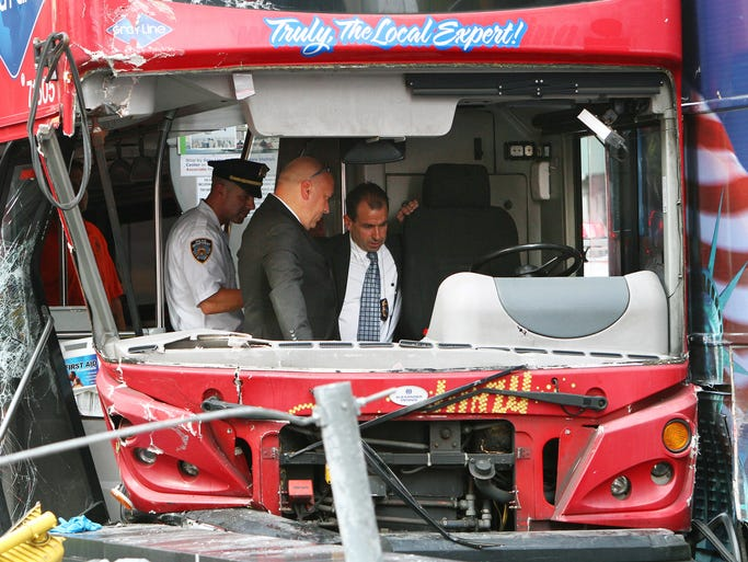 Officials inspect the driver's section of one of the two double-decker buses that collided in Times Square in New York City. Fire department officials said that 13 people were injured but none of the injuries was believed to be life-threatening.