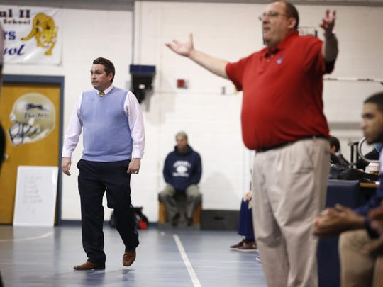 John Paul II coach Titus Nixon, left, squares off against his former coach Danny Serrano at John Paul II Catholic School on Saturday. Nixon played for Serrano, who began the basketball program at John Paul II in 2003 and now coaches the Champagnat Catholic basketball team in Hialeah.