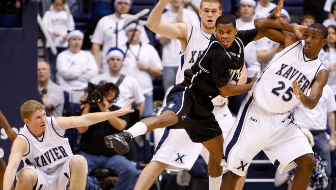 (Left to right) Xavier's Brad Redford, Kenny Frease and Dante Jackson battle Butler's Ronald Nored for a loose ball at Cintas Center in December of 2008.