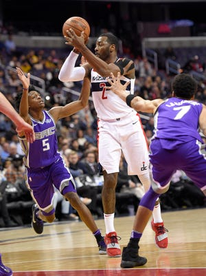 Washington Wizards guard John Wall (2) handles the ball against Sacramento Kings guard De'Aaron Fox (5) and forward Skal Labissiere (7) during the second half of an NBA basketball game, Monday, Nov. 13, 2017, in Washington. The Wizards won 110-92.