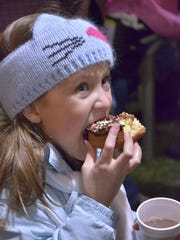 Eight-year-old Andria Ridley enjoys a big doughnut and a cup of hot chocolate before the festivities begin. She attended the opening of the Wayne County Lightfest with her parents, Alex and Jesse Ridley, 2-year-old brother Aiden Ridley and her grandmother, Terri Ridley. They are from Livonia.