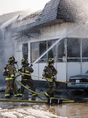 Firefighters aim water into the roof structure at Walsh's Service on Wednesday.