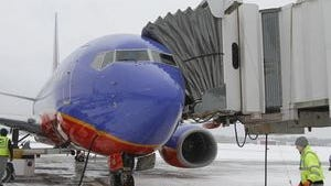 Ben Jones, manager for JetStream Ground Services, moves a safety cone into place after a Southwest Airlines plane parks at a gate at the Rochester airport.