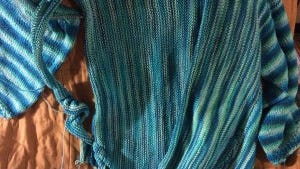 In this photo, you can see the left side with everything finished and the right side, where I have done 14 rows in the front and most of the right sleeve.
