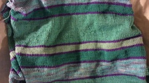 The Mixed Moods sweater has random stripes in shades of aqua and turquoise, defined by thin stripes of purple.
