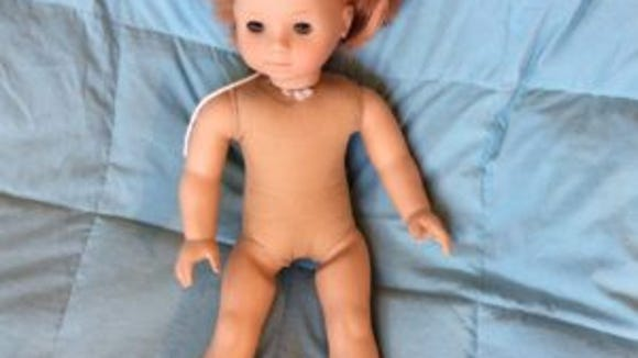 This doll came to me with chopped off hair and stains on her legs and body. This photo was taken after I cleaned her legs.