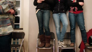 (L-R) Sisters Cassandra Yerkes, 16, and Victoria Yerkes, 17, and their mother Beth Yerkes stand in chairs to get a better view of Republican presidential candidate and former Massachusetts Governor Mitt Romney during a campaign town hall meeting in New Hampshire.