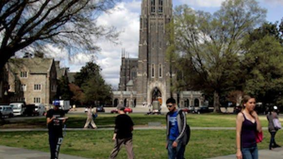 Duke students walk by Duke Chapel on the campus of Duke University in Durham, North Carolina, U.S., on Friday, Mar. 26, 2010. (Photographer: Jim R. Bounds/Bloomberg)