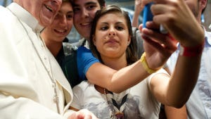 In this file photo Pope Francis has his picture taken inside St. Peter's Basilica with youths from the Italian Diocese of Piacenza and Bobbio. The pope has been praised for his progressive approach of openness and sympathy within the church.