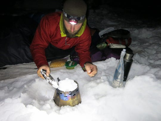 Adventurer Shawn Forry uses a small, alcohol stove to melt snow for water during a winter hike of the Pacific Crest Trail.