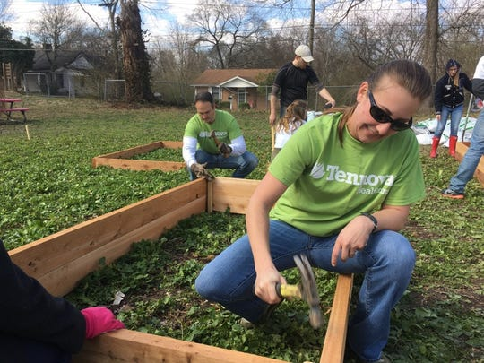 Representing Tennova Healthcare-Clarksville at the community garden Friday were, among others, Kaitlyn Keen, foreground, and Shawn Molsberger.