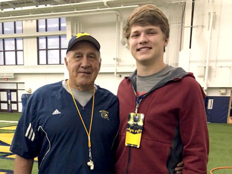 Aidan Hutchinson, right, poses with Michigan defensive line coach Greg Mattison.