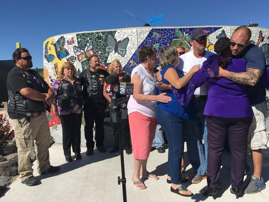 Relatives of Victoria Martens and her godmother Laura Bobbs, second from right, embrace at a children's park in Rio Rancho, N.M., following a news conference Monday, Aug. 29, 2016, to thank the community for their support following the Albuquerque girl's horrific killing last week. Police found Victoria's battered and dismembered body inside the apartment she shared with her mother after responding Aug. 24 to a pre-dawn disturbance.