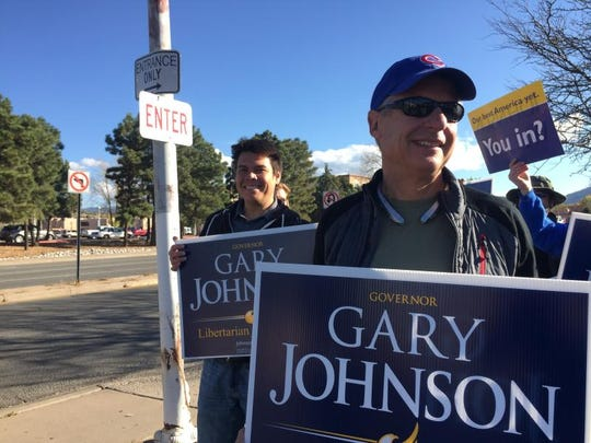 Libertarian Party presidential candidate Gary Johnson joins sign-waving supporters at an intersection outside the state Capitol in Santa Fe, New Mexico, Tuesday, Nov. 8, 2016. Nikos Leverenz, 42, of Sacramento, Calif., left, joins Johnson.
