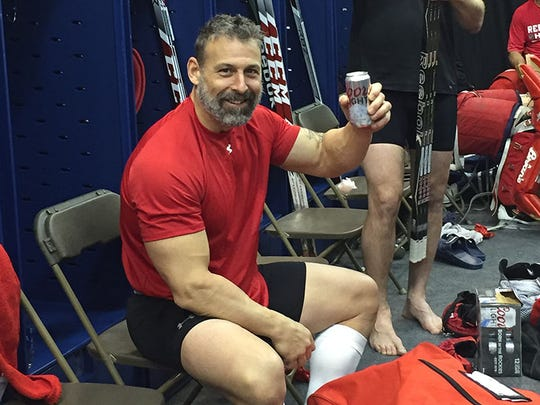 Detroit Red Wings alumnus Martin Lapointe enjoys a cold one after a game against the Colorado Avalanche alumni in February 2016.