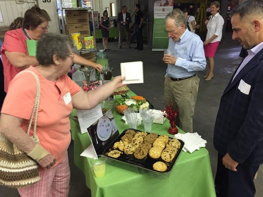Grace Cecil, a Power Packs volunteer from St. Luke's Church, shows a recipe for Porcupine meatballs to Mike Valudes of Yocum & Co. at Friday's ribbon cutting of Power Packs new warehouse in West Lebanon Township.