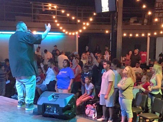Phillip Juarez sings in front of a crowd. His christian music is far from the street lifestyle that he used to rap about.