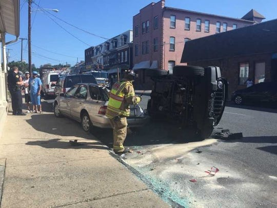 A Lebanon firefighter begins cleaning up a crash that occurred at N. Ninth and Lehman streets at 9:25 a.m. Thursday. A woman driving the black Jeep was transported to a hospital. A police report was not available.