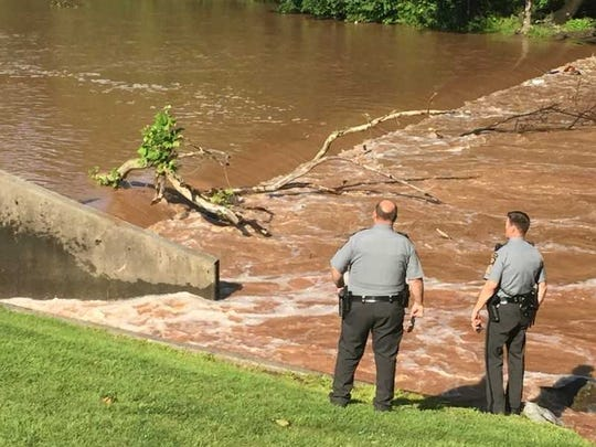 Pennsylvania State troopers look at the turbulent water of a low head dam in Swatara Creek where a Cleona man drowned on July 1.