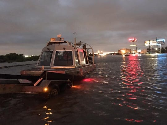 Coast Guard airboat is launched to assist evacuation of a hospital in the background.