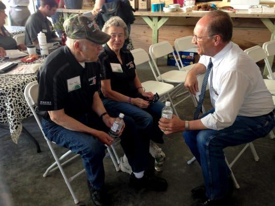 Then-Wisconsin agriculture secretary Ben Brancel meets with Henry and Carol Ebert during Farm Technology Days in Algoma, Wis. Brancel, who retired in August, says the United States should change immigration law to accommodate the growing number of immigrants working in the dairy industry.