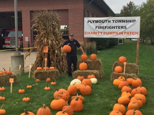 Firefighter Pete Bukis stands in one of the two pumpkin
