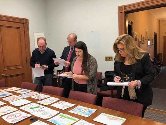 Judges review the artwork submitted by children in