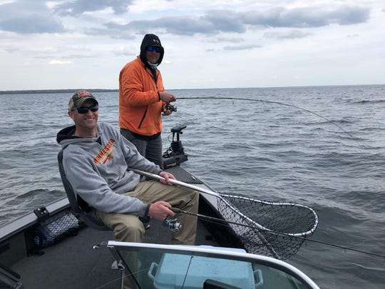 Josh Berg from Alexandria waits to net a fish being fought by Fred Moyer of Andover Saturday morning on a shallow, wind swept flat.