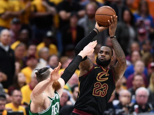 Cavaliers forward LeBron James (23) attempts a three point shot over Boston Celtics center Aron Baynes (46) during the forth quarter in game four of the Eastern conference finals of the 2018 NBA Playoffs at Quicken Loans Arena.