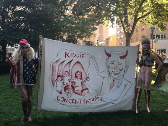 Two protestors in Rittenhouse Square hold up a sign