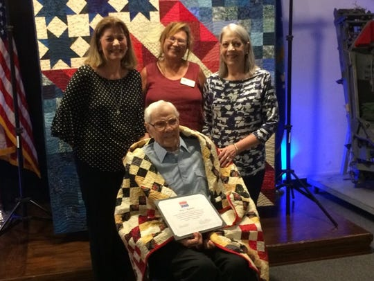 U.S. Marine Corps Veteran Roy Buckner, wrapped in his Quilt of Valor (clockwise, from seated), daughter Sandy Stentz; Renee Hoeprich, president of Giving Quilts, Baton Rouge; and Buckner's daughter, Terri Pawliski