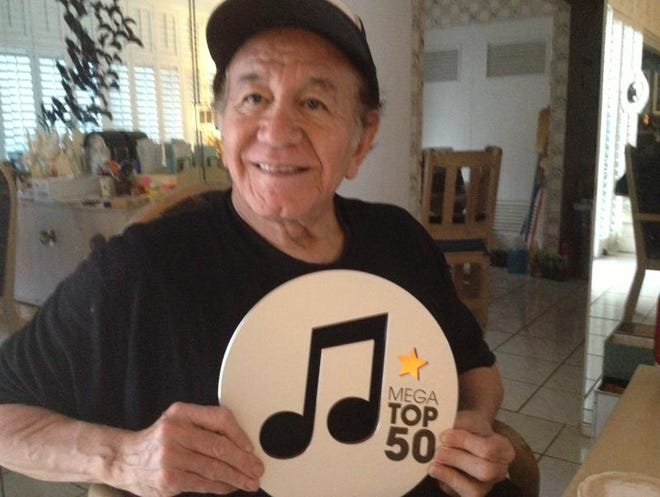 Late Palm Springs resident Trini Lopez shows off an award he received for having the first-ever No. 1 hit on the Dutch charts over 50 years ago. Heritage Auctions announced they will auction 90 items owned by Lopez, which includes five of his guitars.