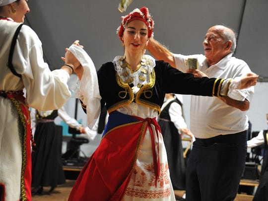 Maria Sofikitis (center), 20,  and the Pride of Greece dancers perform as Elias Nyktas (right), of Jensen Beach, throws money in support during St. John Chrysostom Greek Orthodox Church's  2015 Greek Festival. This year's festival is  Thursday through Sunday in Hobe Sound.