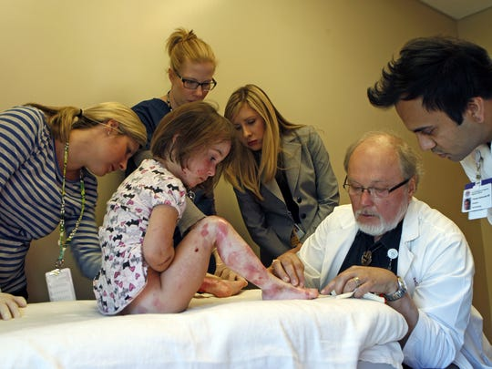 Lizzy Hendrickson is examined by Dr. Ron Hansen (seated