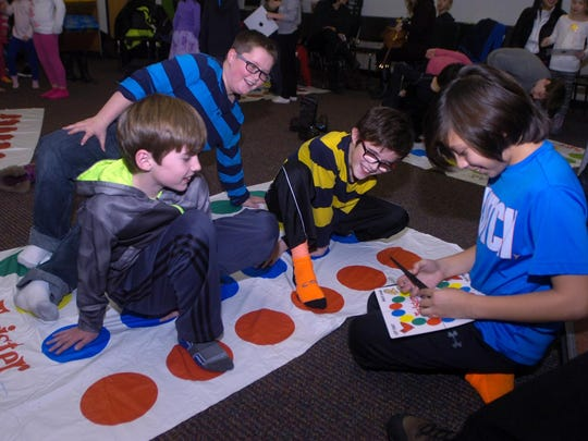 Ethan Gleaser (right) calls out the next move in a game of Twister.