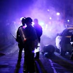 FILE - In this Nov. 25, 2014 file photo, police officers watch protesters as smoke fills the streets in Ferguson, Mo. after a grand jury's decision in the fatal shooting of Michael Brown. A Justice Department investigation has found patterns of racial bias in the Ferguson police department and at the municipal jail and court. The full report, to be publicly released on March 4, says the investigation found Ferguson officers disproportionately used excessive force against blacks and too often charged them with petty offenses. (AP Photo/Charlie Riedel, File)