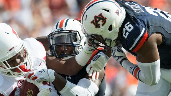 Auburn linebackers JaViere Mitchell and Justin Garrett (26) make a tackle against Arkansas. Garrett is the only player on the Auburn roster that have won a bowl game.