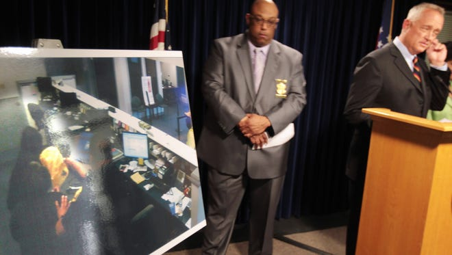 Hamilton County Prosecutor Joseph Deters speaks alongside Cincinnati Police Chief Eliot Isaac at a press conference about a Wednesday, May 25, shooting at a Madisonville Fifth Third bank. A photo of bank surveillance shows CPD officer Kevin Hankerson pushing a bank teller aside as his pistol points at Terry Frost III.