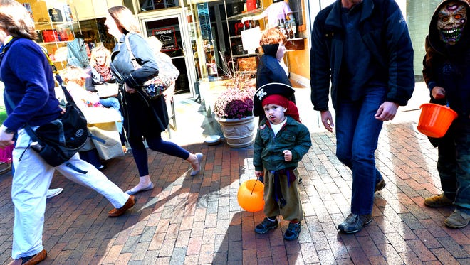 "A young ""pirate"" looks around while walking through downtown Staunton trick-or-treating with others on Saturday, Oct. 26, 2013."