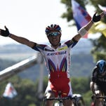 Joaquim Rodriguez celebrates as he crosses the finish line ahead of Christopher Froome at the end of the third stage of the 102nd Tour de France on Monday.