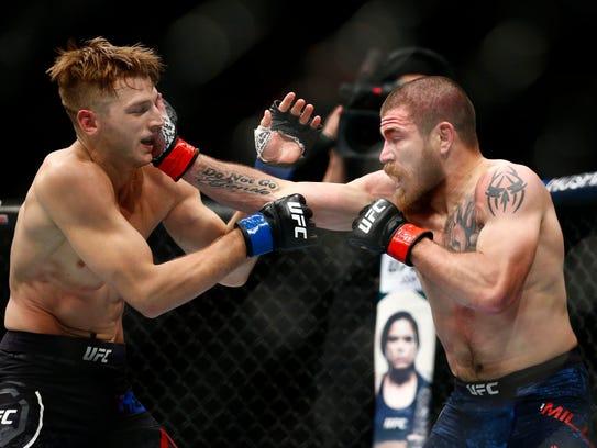 Dan Hooker (blue gloves) fights Jim Miller (red gloves)