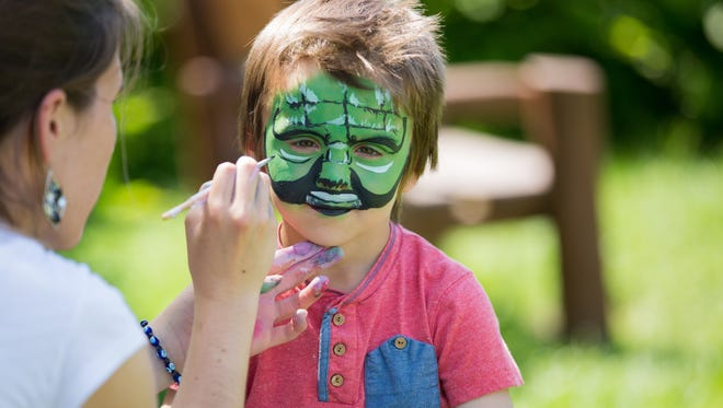 Child having face painted.