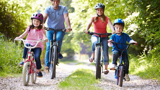 Family On Cycle Ride In Countryside Smiling At Camera