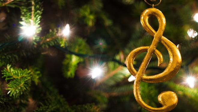 Gold treble clef ornament hanging on a Christmas Tree.