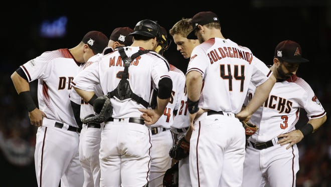 Arizona Diamondbacks pitcher Zack Greinke huddles on the mound against the Los Angeles Dodgers in the 3rd inning during Game 3 of the NLDS on Monday, Oct. 9, 2017 at Chase Field in Phoenix, Ariz.